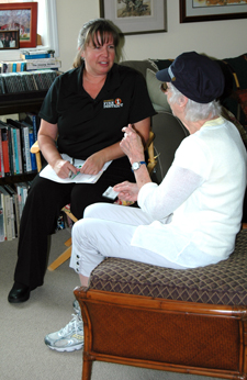 Community resource specialist talks with client at home