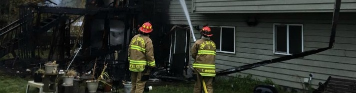 firefighters hose down a house fire