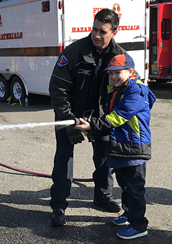 Kid with firefighter spraying water from hose