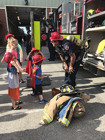 Firefighter showing kids fire engine