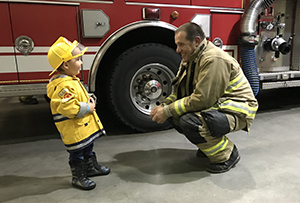 firefighter with boy in front of fire truck