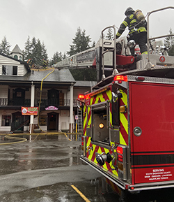 Firefighters using ladder truck to access restaurant roof