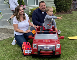 Eli and his family with toy fire truck