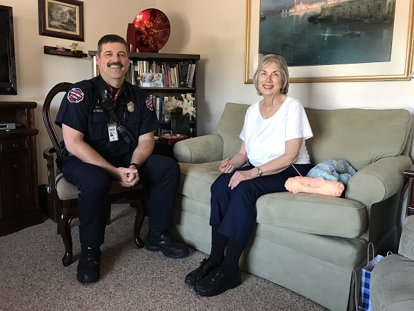 community paramedic sits with woman in a home
